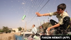 Iranian police dump confiscated beer cans in Tehran on July 22, 2009. FILE PHOTO