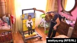 Мать тройняшек Гульмира помогает одному из близнецов делать упражнения. Алматинская область, апрель 2017 года.