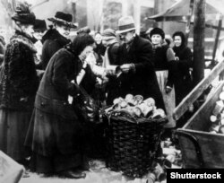A woman selling tin cans on the streets of Berlin in 1923 amidst poverty and dizzying hyperinflation.