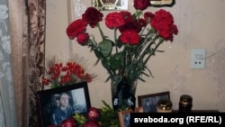Flowers and photos of Uladzislau Kavalyou on a table in the apartment of his mother in Minsk