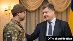 Украина президенті Петр Порошенко тұтқыннан босатылған сарбаз Андрей Гречановпен сөйлесіп тұр.