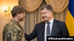 Президент Петро Порошенко туткундан бошонгон аскер Андрей Гречанов менен.