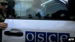 Член місії ОБСЄ йде з будівлі місцевої адміністрації в Слов'янську, де утримують заручників, 27 квітня 2014 року
