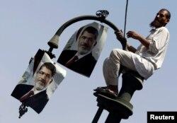 Прихильник Мухаммада Мурсі розвішує його портрети на ліхтарі біля будівлі Генеральної прокуратури Єгипту, Каїр, 22 липня 2013 року