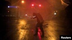 Человек пытается устоять на ногах во время сильного шторма. Штат Техас, США, 25 августа 2017 года.