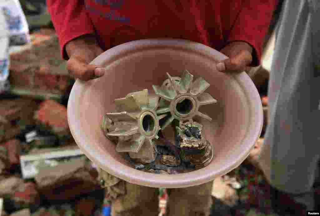 A Pakistani villager holds up a pot with fragments of mortar shells, which locals say were fired from the Indian side of the disputed border in Kashmir.