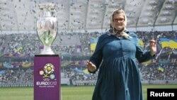 Женщина позирует рядом с экраном, на котором показывают кубок EURO-2012. Киев, Украина.