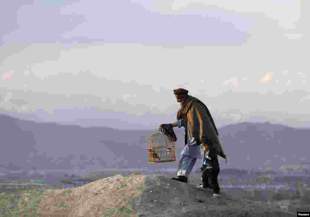 An Afghan man holds onto a child as he walks with a cage of quails on a hill in Kabul on April 23. (Reuters/Mohammad Ismail)
