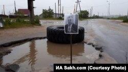 Портрет мэра Охи в в дорожной яме