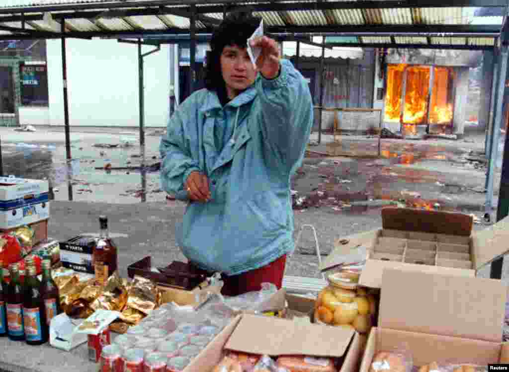 A Serb woman sells goods in a market as a shop burns behind her in Ilidzia, a Serb-held suburb of Sarajevo on March 9, 1996, three days before it was due to come under Croat and Muslim rule.