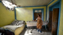 A woman shows damage to her house after suspected shelling by Armenian forces in the Tovuz region of Azerbaijan on July 14.