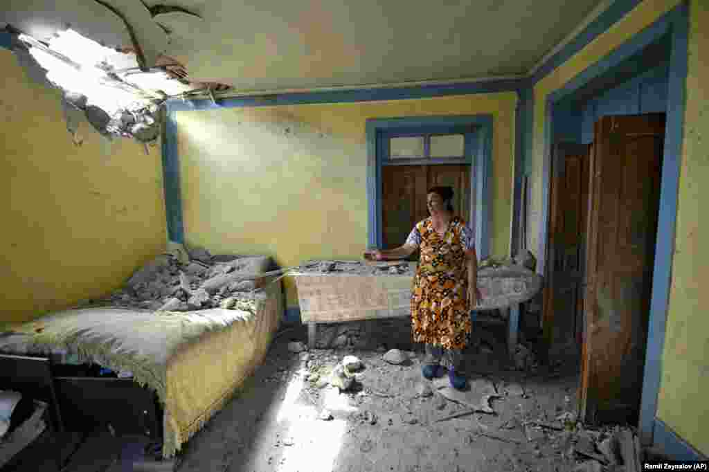 A local Azerbaijani woman shows damage in her house after shelling by Armenian forces in the Tovuz region on July 14. (AP/Ramil Zeynatov)