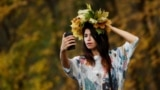RUSSIA -- A woman takes a selfie with yellow leaves in a park in Moscow, Russia October 14, 2020.