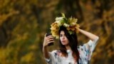 A woman takes a selfie with yellow leaves in a park in Moscow. (Reuters/Maxim Shemetov)