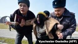 Милиционеры уводят участницу «Марша женской солидарности» в Бишкеке. 8 марта 2020 года.