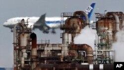 In this Thursday, Dec. 13, 2018 photo a passenger plane prepares for landing near an oil refinery in Kawasaki, southwest of Tokyo. (AP Photo/Koji Sasahara)