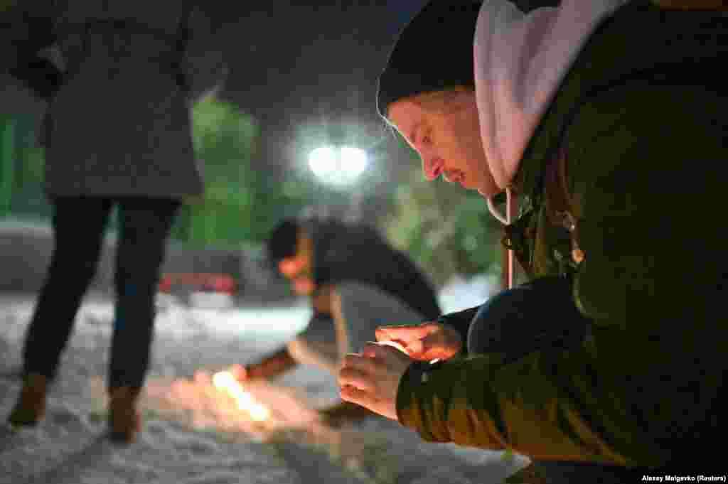 Suporterii lui Navalnîi aprind lumânări într-o curte din Omsk.