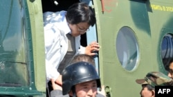 Interim leader Roza Otunbaeva exits her helicopter upon arrival in Osh on June 18.