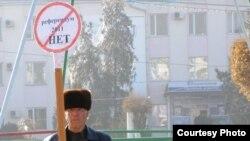 """Житель Тараза Акыл Бейсембаев стоит возле здания регионального офиса президентской партии """"Нур Отан"""" со знаком, на котором написано «Референдум 2011 НЕТ». Тараз, 12 января 2011 года. Фото предоставлено жамбылским филиалом партии """"Алга""""."""