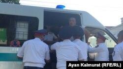 Полиция қызметкерлері Астана алаңында ұстаған адамды көлікке салып жатыр. Алматы, 6 шілде 2018 жыл.