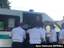 Полицейские заталкивают задержанного рядом с площадью Астана человека в служебный микроавтобус. Алматы, 6 июля 2018 года.
