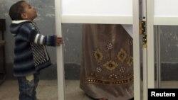 Мальчик стоит возле кабины для тайного голосования в день парламентских выборов в Египте. 3 января 2012 года. Иллюстративное фото.