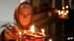 Женщина зажигает свечи в церкви села Кущевская в Краснодарском крае России. 20 ноября 2010 года.