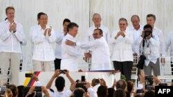 """Kolumbiýanyň prezidenti Huan Manuel Santos (çepde) we """"FARC"""" pitneçi topardan Timoleon Jimenez aka Timoçenko elleşip salamlaşýar."""