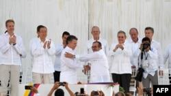 Президент Колумбии Хуан Мануэль Сантос и глава ФАРК Родриго Лондоно также известный как Тимолеон Хименес после подписания договора