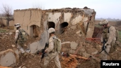FILE: U.S. Marines walk through the rubble of a house destroyed in an airstrike in Helmand.