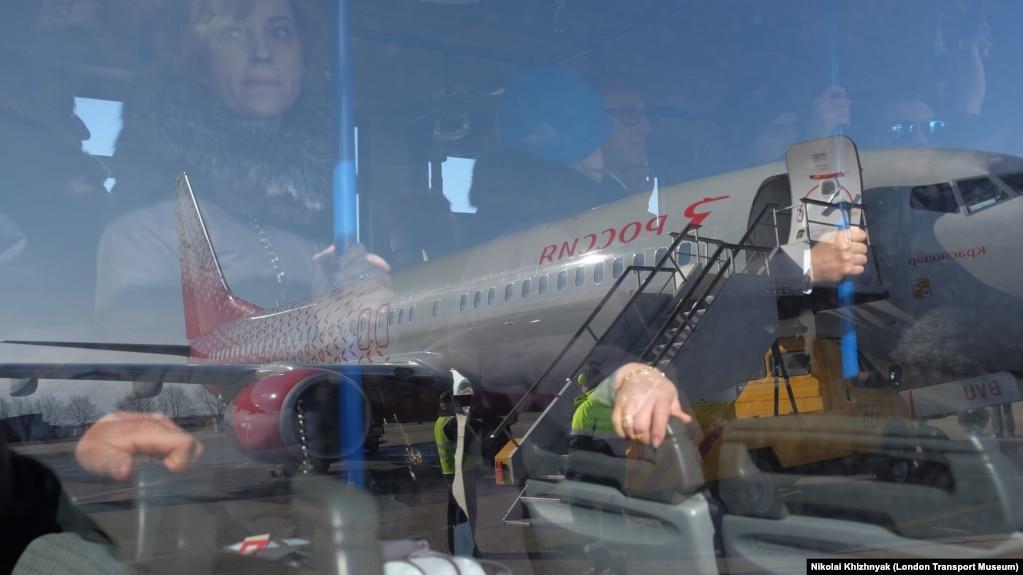 «Россия» әуе компаниясы ұшағы жанынан өтіп бара жатқан автобустағы жолаушылар. Көрнекі сурет.