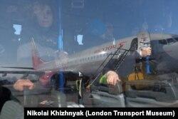 Пассажиры в салоне аэродромного автобуса, проезжающего рядом с самолетом авиакомпании «Россия». Иллюстративное фото.