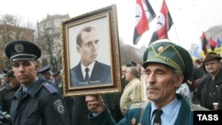 Members of a World War II guerrilla movement, the Ukrainian Insurgent Army (UPA), hold a portrait of UPA leader Stepan Bandera in Kyiv.