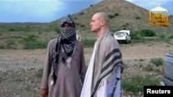 US Army Sergeant Bowe Bergdahl (R) waits before being released at the Afghan border, in this still image from video released June 4, 2014.
