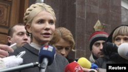 Former Ukrainian Prime Minister Yulia Tymoshenko talks to the media as she arrives at the state prosecutor's office in Kyiv on December 15