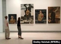 Посетители в зале, где выставлены портреты Гитлера