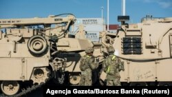 Военные рядом с военной техникой, доставленной из США в Гданьск а рамках миссии НАТО. 13 сентября 2017 года.