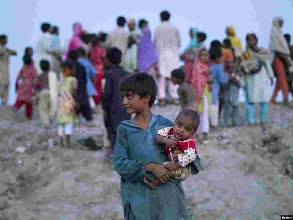 A boy holds his sibling as flood victims wait on a roadside for food handouts from motorists in Pakistan's Muzaffargarh district in Punjab Province on August 11. Photo by Adrees Latif for Reuters