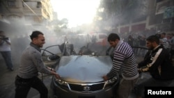 Palestinians try to remove the remains of a car after an Israeli air strike in Gaza City on November 14.