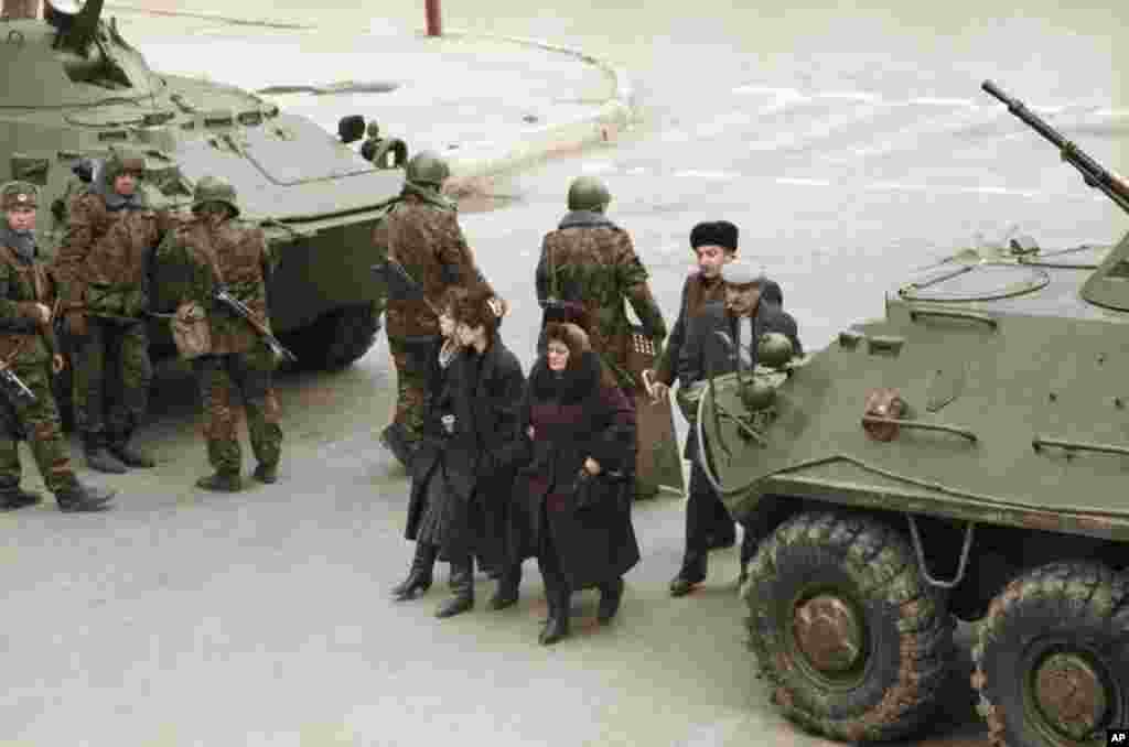 Azerbaijani women walk between a pair of Soviet tanks in Baku on January 28.