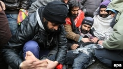 Asylum seekers from Afghanistan rub a fellow protester's feet against the cold as they gather to protest at the 'Grand Place' in Mons, Belgium. (file photo)