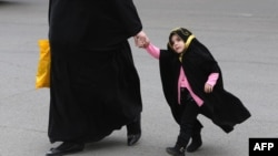 Молодая мусульманка-мать на прогулке с маленькой дочерью в покрытии. Архивно-иллюстративное фото, 2014. Иллюстративное фото.