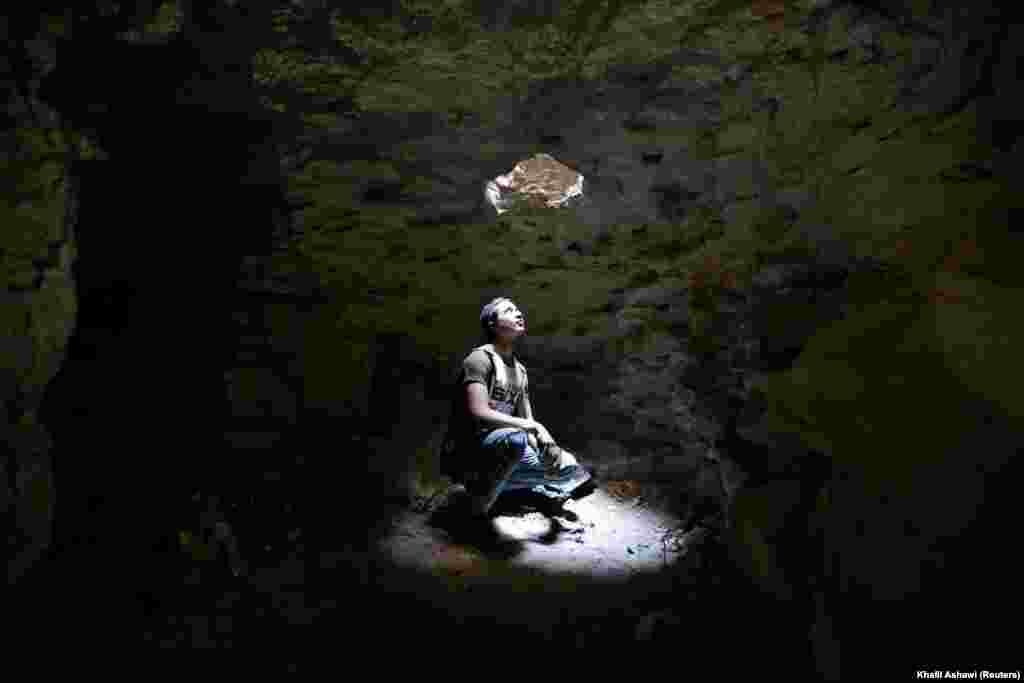 Чалавек глядзіць праз адтуліну самаробнага прытулку ў падземнай пячоры ў Ідлібе, Сырыя, 3 верасьня.