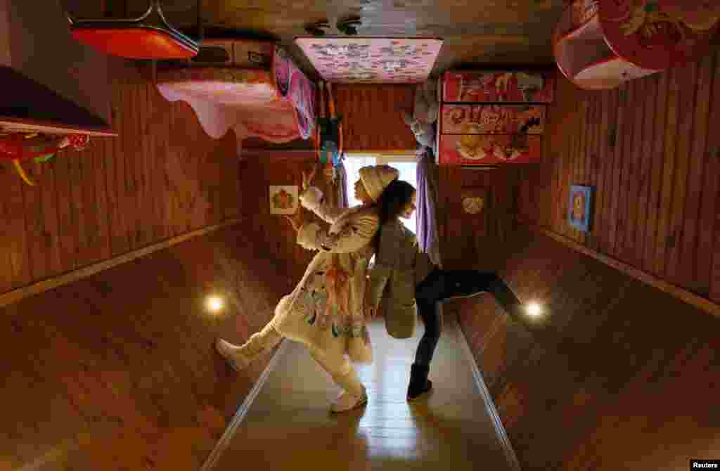 A visitor and an employee dressed as Snegurochka (Snow Maiden), the granddaughter of Ded Moroz (Russian equivalent of Santa Claus), pose for a picture inside an upside-down house in the suburbs of Krasnoyarsk, Russia. (Reuters/Ilya Naymushin)