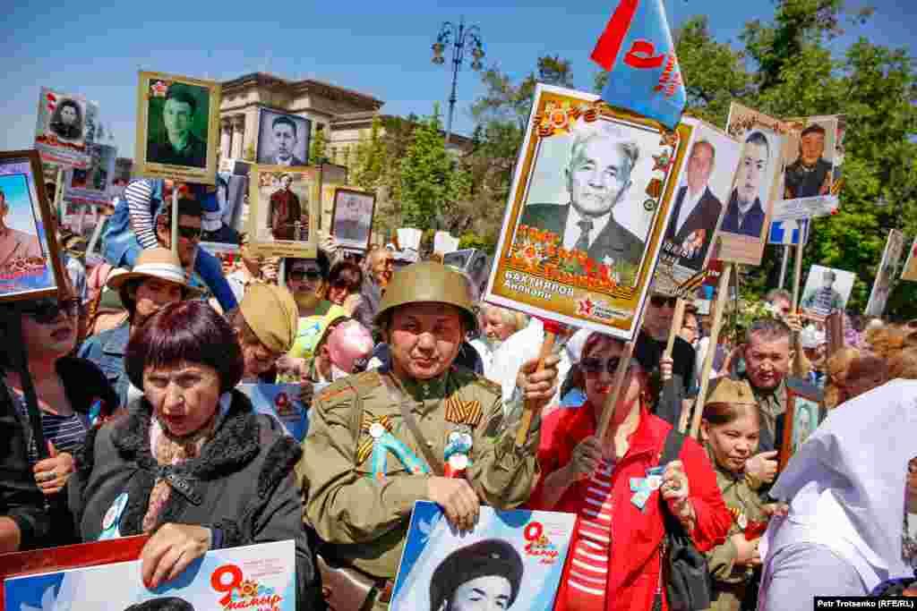 Мужчина держит портрет родственника во время акции «Бессмертный полк» в Алматы, 9 мая 2019 года.