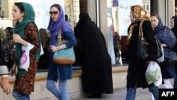 Иранские женщины, одетые в джинсы, идут по улице. Тегеран, 7 октября 2013 года.