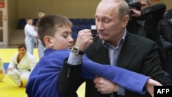 Russian Prime Minister Vladimir Putin (right) gets to grips with a young judo wrestler at a regional judo center in Siberia.