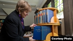 Dean Martha Roth, the editor-in-charge of the Assyrian dictionary, places the final volume to be completed among the others. (photo: University of Chicago -- Jason Smith)
