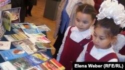 """Девочки рассматривают книги на экомарафоне """"Знатоки природы"""". Караганда, 22 мая 2014 года."""