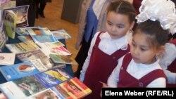 «Табиғат білгірлері» экомарафонында кітап қарап тұрған балалар. Қарағанды, 22 мамыр 2014 жыл.